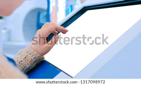 Woman using interactive digital informational kiosk with touchscreen display at urban exhibition - scrolling and touching. Education, mockup, template and technology concept #1317098972