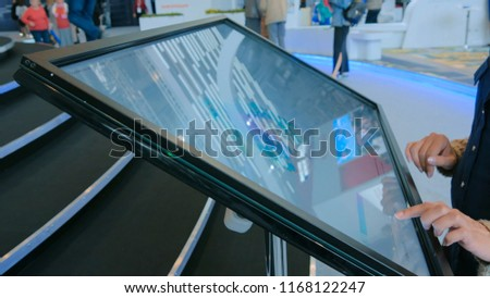 Woman using interactive touchscreen display at urban exhibition - scrolling and touching. Education and technology concept #1168122247