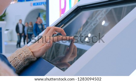 Woman using interactive touchscreen display at urban exhibition - scrolling and touching. Education and technology concept #1283094502