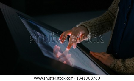 Woman using interactive touchscreen display in modern historical museum. Evening time, lowlight. Education and entertainment concept. Close up shot #1341908780