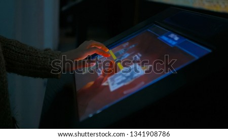 Woman using interactive touchscreen display in modern historical museum. Evening time, lowlight. Education and entertainment concept. Close up shot #1341908786
