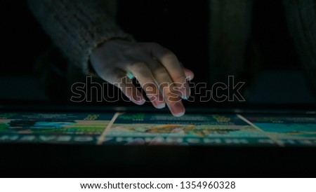 Woman using interactive touchscreen display in modern historical museum. Evening time, lowlight. Education and entertainment concept. Close up shot #1354960328
