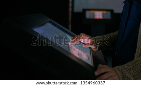 Woman using interactive touchscreen display in modern historical museum. Evening time, lowlight. Education and entertainment concept. Close up shot #1354960337