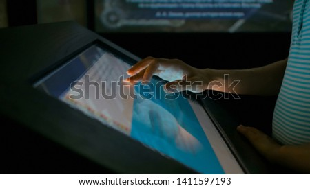 Woman using interactive touchscreen display in modern historical museum. Evening time, lowlight. Education and entertainment concept. Close up shot #1411597193