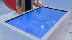 Woman using interactive touchscreen display table at urban exhibition - scrolling and touching