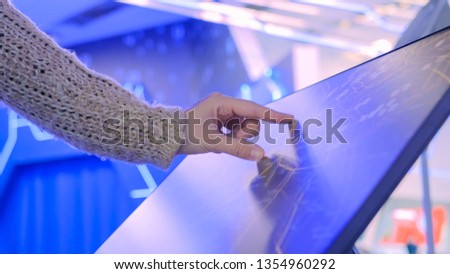 Woman using interactive touchscreen display with unrecognizable virtual map at modern technology show with futuristic interior #1354960292