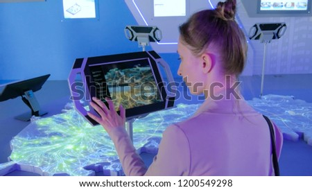 Woman using interactive touchscreen display with virtual map of Moscow at modern technology show #1200549298