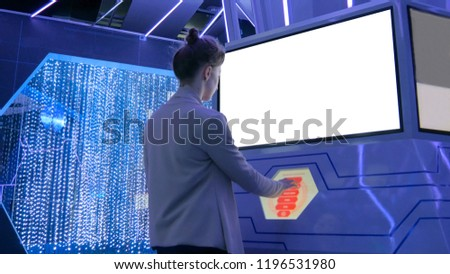 Woman using interactive touchscreen display with white blank screen at modern technology show #1196531980