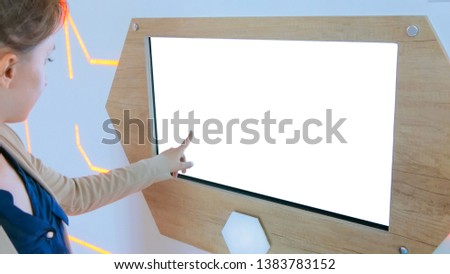Woman using interactive touchscreen kiosk with white empty screen at modern history museum - scrolling and touching. Education, mock-up, template and technology concept #1383783152