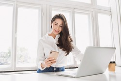 Woman using laptop and smartphone in office. Beautiful girl texting on phone. Entrepreneur, businesswoman, freelance worker, student working on computer at home. Business, technology concept