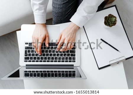 Woman using laptop at workplace in office. Flatlay photo, space for text.