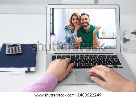 Woman using laptop for conversation via video chat at table, closeup