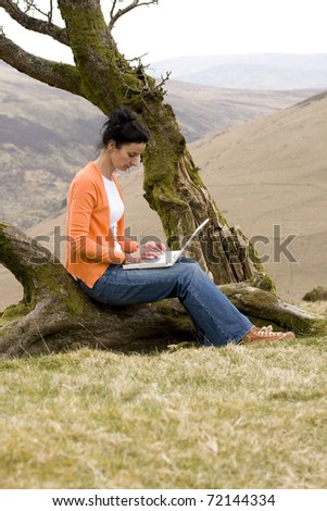 woman using laptop in park and sending e-mail