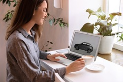 Woman using laptop to buy car at table indoors