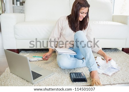 Woman using laptop to calculate bills on floor of living room