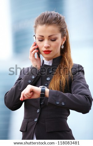 Businesswoman with umbrella fighting with rain and strong wind
