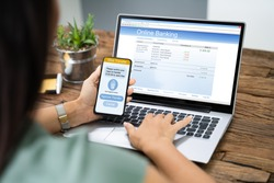 Woman Using Mobile Phone App To Authenthificate Bank Transfer On Laptop