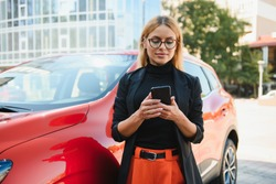 Woman using mobile phone, communication or online application, standing near car on city street or parking, outdoors. Car sharing, rental service or taxi app.