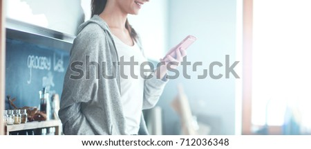 Woman using mobile phone sitting in modern kitchen #712036348