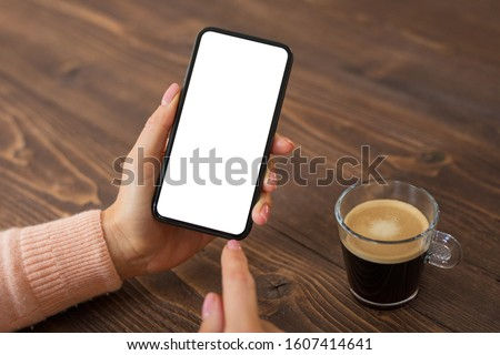 Photo of  Woman using mobile phone. Smartphone mockup with empty white screen.