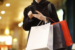 Woman Using Mobile Phone While Holding Shopping Bags