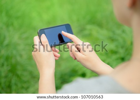 Woman using mobile smart phone in the park.