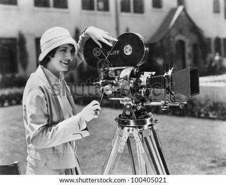 Woman using movie camera outdoors
