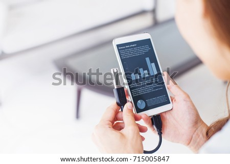 woman using otg usb with her mobile phone to see graphs
