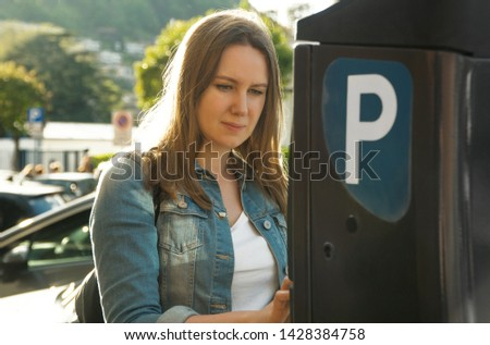 Woman using parking machine on the street.