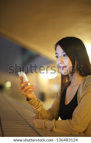 woman using phone in city at night