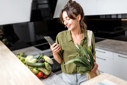 Woman using phone while standing with shopping bag and healthy fresh food on the kitchen at home
