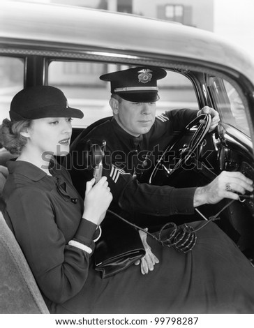 Woman using radio in car with policeman - stock photo