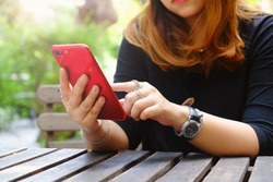 woman using red smart phone in the garden