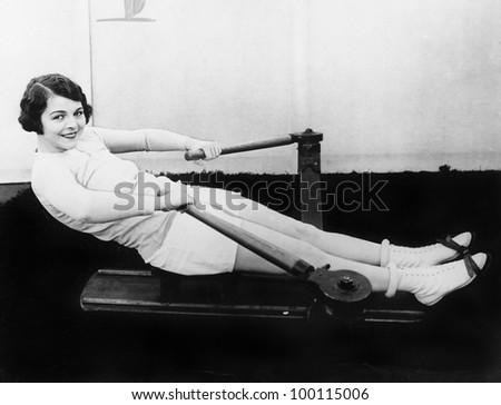 Woman using rowing machine Zdjęcia stock ©