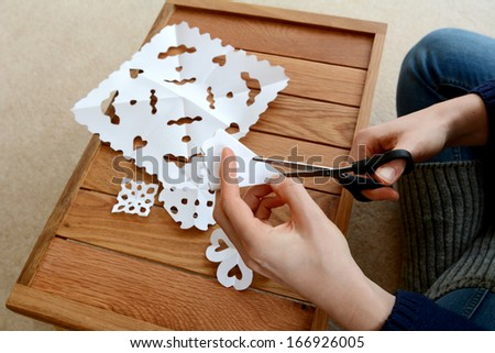 Woman using scissors to cut folded white paper into snowflake designs