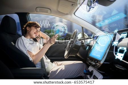 woman using smart phone in autonomous car. self driving vehicle. driverless car. autopilot. automotive technology.