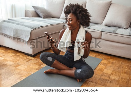 Woman using smart phone on exercise mat in front of her laptop. Sporty girl is exercising at phone on mat enjoying playlist on mobile phone. Positive active energtic sportswoman sit on mat use phone