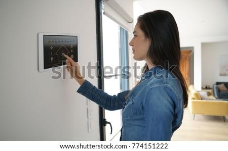 woman using smart wall home...