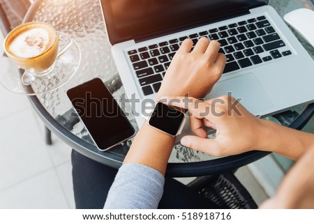woman using smart watch in coffee shop, modern city lifestyle #518918716
