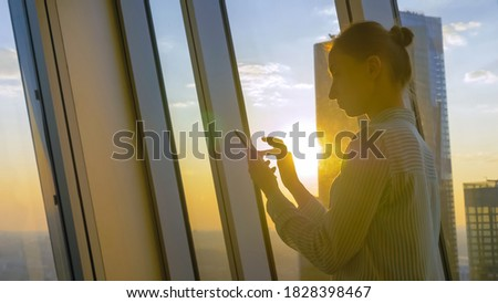 Woman using smartphone against sunset cityscape view through window of skyscraper: scrolling and touching. Sun lens flare, golden hour. Leisure time, sightseeing, technology concept Foto d'archivio ©