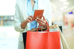 Woman using smartphone and holding shopping bag while standing on the mall background.