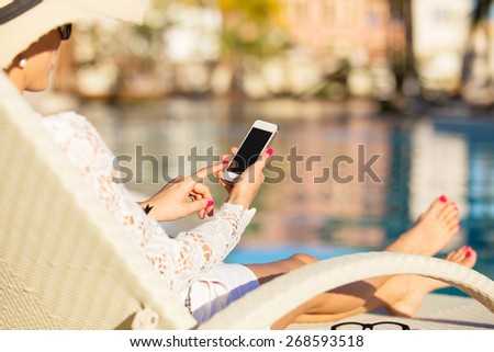 Woman using smartphone by the pool #268593518