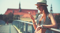 Woman using smartphone in the European city. Hipster girl browsing Internet on a phone, texting and communicating outdoors. Travel concept