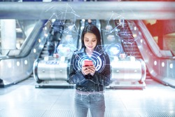 Woman using smartphone, network and communication, modern background - Asian young woman with empty escalator at train station connecting to fast internet - technology and 5g development