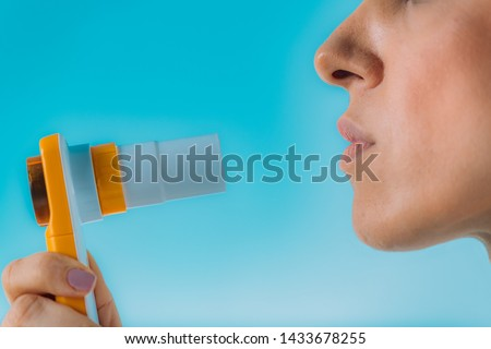 Woman using Spirometer  Measuring Lung Capacity