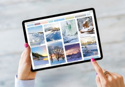 Woman using tablet and browsing beautiful winter photography online