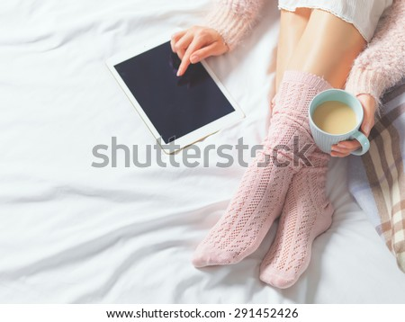 Woman using tablet at cozy home atmosphere on the bed. Young woman with cup of cocoa or coffee in hands enjoying free time with comfort. Soft light and comfy lifestyle concept. Technology in life.