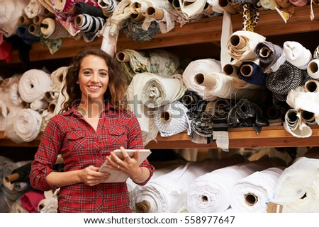 Woman using tablet in fabric storage warehouse, portrait