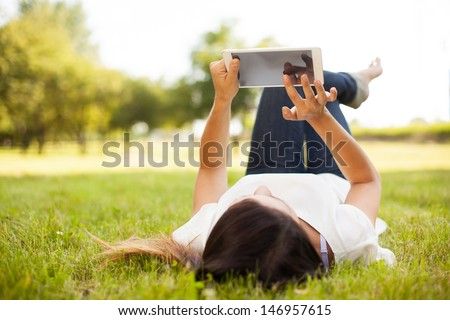 Woman using tablet outdoor laying on grass