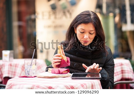 Woman using tablet outdoors sit in a bar. Shallow depth of field.